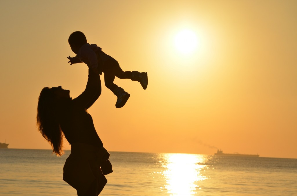 mother-lifting child at sunset